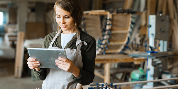 Woman wearing work apron standing in her workshop looking at a tablet