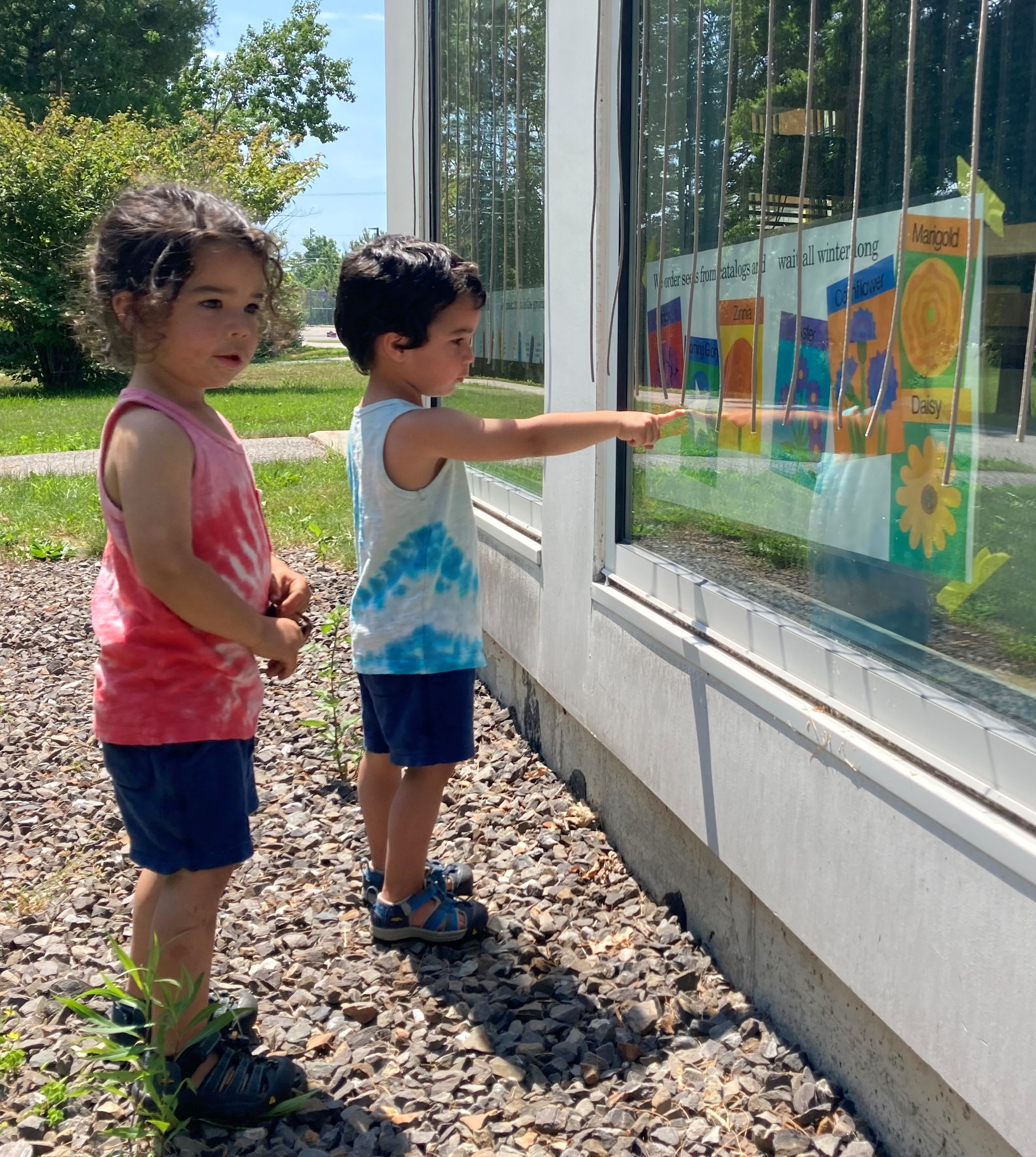 Siblings reading large-format pages of a book on the Scarborough Public Library's Story Walk